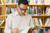 Concentrated mature student reading book in library — Stock Photo