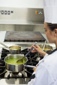 Young chef stirring sauce — Stock Photo