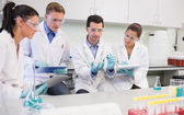 Scientists with tablet PC working on an experiment at lab — Stock Photo