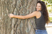 Casual attractive brunette embracing a tree with closed eyes — Stock Photo