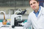 Smiling scientific researcher with microscope in laboratory — Stock Photo