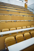Empty seats with tables in a lecture hall — Stock Photo