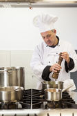Concentrating head chef using pepper mill — Stock Photo