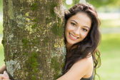 Casual smiling brunette embracing a tree looking at camera — Stockfoto