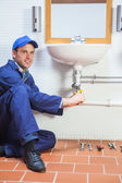Smiling plumber repairing sink — Stock Photo