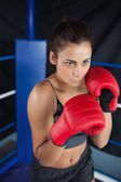 Determined woman in red boxing gloves — Stock Photo