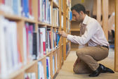 Handsome casual man cowering in front of bookshelves — Stock Photo
