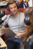 Attractive happy radio host interviewing a guest holding clipboa — Stock Photo