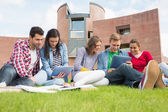 Students using tablet PCs in the lawn against college building — Stock Photo