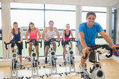 Happy man teaches spinning class to four people — Foto Stock