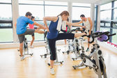 People warming up by exercise bikes in spinning class — Stock Photo