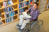 Man in wheelchair by bookshelf in the library — Stock Photo