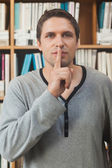 Male librarian making a sign to be quiet in library — Stock Photo