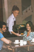 Smiling waitress serving food to a couple — Stockfoto