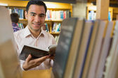 Smiling mature student with book by shelf in library — Stock Photo