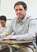 Portrait of a mature student taking notes in classroom — Stock Photo