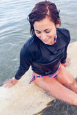 Beautiful young woman sitting on surfboard in water — Foto Stock