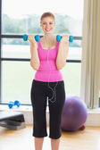 Fit woman exercising with dumbbells in fitness studio — Stock Photo