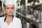 Young unsmiling chef standing arms crossed between shelves — Stock Photo
