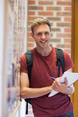 Handsome smiling student taking notes next to notice board — Stock Photo
