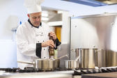 Focused head chef flavoring food with pepper — Stock Photo