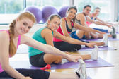 Portrait of fitness class and instructor stretching legs — Stock Photo