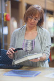 Mature female librarian scanning book — Stock Photo