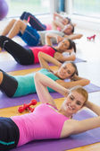 Sporty fitness class doing sit ups on exercise mats — Stock Photo