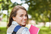 Pretty cheerful student smiling at camera carrying notebook — Stock Photo