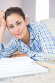 Portrait of calm young student doing assignments while lying on — Stock Photo