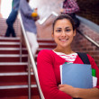 Smiling female holding books with students on stairs in college — Stock Photo #36170191