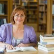 Smiling mature female student at desk in the library — Stock Photo