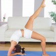 Profile view of slim woman practicing yoga pose on exercise mat — Stock Photo