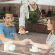 A couple holding hands while waitress serving food — Stock Photo #36170721