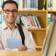Smiling mature student with tablet PC in library — Stock Photo #36170953