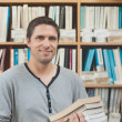 Mature student standing in a library holding some books — Stock Photo