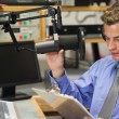 Stock Photo: Well dressed focused radio host moderating