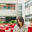 Sad student in the cafeteria with food tray — Stock Photo