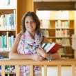 Female student with books standing in the library — Stock Photo