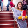 Female holding books with students on stairs in college — Stock Photo #36171087
