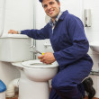 Good looking plumber repairing toilet — Foto Stock