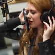 Stock Photo: Concentrating beautiful singer recording a song