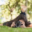 Young woman using her camera for taking a picture lying on a law — Stock Photo #36171123