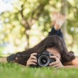 Young womusing her camerfor taking picture lying on law — Stock Photo #36171123