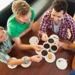 Four happy students having a cup of coffee chatting — Stock Photo