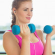 Woman exercising with dumbbells in fitness studio — Stock Photo