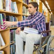Man in wheelchair selecting book in library — Stock Photo #36171337