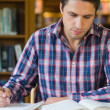 Male student writing notes at desk in the library — Stock Photo