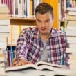 Stock Photo: Handsome student studying between piles of books