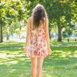 Rear view of beautiful stylish brunette walking on grass — Stock Photo #36172087